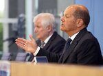Federal Minister of Finance Olaf Scholz, right, and Federal Minister of the Interior Horst Seehofer attend a press conference on federal flood aid in Berlin, Germany, Wednesday, July 21, 2021. (AP Photo/Axel Schmidt, Pool)