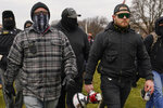 FILE - In this Jan. 6, 2021, file photo, Proud Boys members Joseph Biggs, left, and Ethan Nordean, right with megaphone, walk toward the U.S. Capitol in Washington, in support of President Donald Trump. Four men described by prosecutors as leaders of the far-right Proud Boys have been indicted on charges that they planned and carried out a coordinated attack on the U.S. Capitol to stop Congress from certifying President Joe Biden's electoral victory. Nordean and Biggs, two of the four defendants charged in the latest indictment, were arrested several weeks ago on separate but related charges. The new indictment also charges Zachary Rehl and Charles Donohoe.(AP Photo/Carolyn Kaster, File)