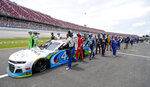 FILE - In this Monday June 22, 2020 file photo, NASCAR drivers Kyle Busch, left, and Corey LaJoie, right, join other drivers and crews as they push the car of Bubba Wallace to the front of the field prior to the start of the NASCAR Cup Series auto race at the Talladega Superspeedway in Talladega Ala. On Friday, June 26, 2020, The Associated Press reported on stories circulating online incorrectly asserting NASCAR allows a Black Lives Matter-themed car, but won't allow its audience to wear MAGA hats or other Trump clothing. The auto racing association has not banned Trump-themed clothing, according to NASCAR spokesman Mike Forde. (AP Photo/John Bazemore)