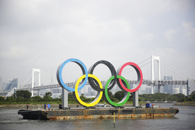 "A symbol installed for the Olympic and Paralympic Games Tokyo 2020 on a barge is moved away from its usual spot by tugboats off the Odaiba Marine Park in Tokyo Thursday, Aug. 6, 2020. The five Olympic rings floating on a barge in Tokyo Bay were removed for what is being called ""maintenance,"" and officials says they will return to greet next year's Games. The Tokyo Olympics have been postponed for a year because of the coronavirus pandemic and are to open on July 23, 2021. The Paralympics follow on Aug. 24. (AP Photo/Hiro Komae)"
