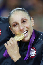 FILE - United States' Diana Taurasi bites her gold medal after beating France in the women's gold medal basketball game at the 2012 Summer Olympics, in London, in this Saturday, Aug. 11, 2012, file photo. Sue Bird and Diana Taurasi will try and become the first five-time Olympic gold medalists in basketball as they lead the U.S women's team at the Tokyo Games. The duo was selected for their fifth Olympics on Monday, June 21, 2021, joining Teresa Edwards as the only basketball players in U.S. history to play in five.(AP Photo/Charles Krupa, File)
