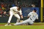 Milwaukee Brewers' Jace Peterson (14) is tagged out while trying to steal third by San Francisco Giants third baseman Kris Bryant during the fourth inning of a baseball game in San Francisco, Monday, Aug. 30, 2021. (AP Photo/Jeff Chiu)