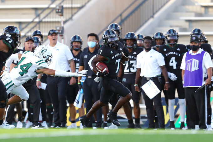 Hawaii running back Calvin Turner Jr. (7) runs the ball after making catch, just out of reach of Portland State safety Anthony Adams (14) during the first half of an NCAA college football game Saturday, Sept. 4, 2021, in Honolulu. (AP Photo/Darryl Oumi)