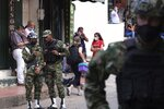 Soldiers listen to news on a mobile phone near the military base where a car bomb exploded in Cucuta, Colombia, Tuesday, June 15, 2021. Colombian authorities still have not confirmed how many were injured in the explosion. (AP Photo/Ferley Ospina)