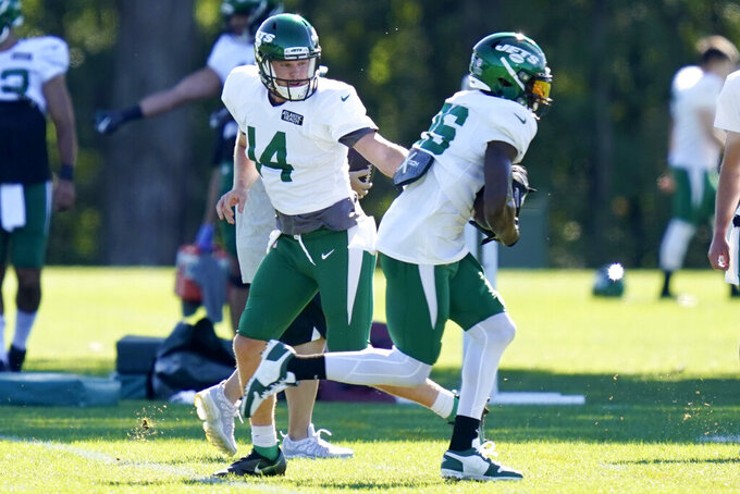 New York Jets quarterback Sam Darnold, left, hands off to Le'Veon Bell during practice at the NFL football team's training camp in Florham Park, N.J., Thursday, Aug. 20, 2020. (AP Photo/Seth Wenig)