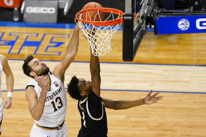 Wake Forest forward Isaiah Mucius (1) takes a shot as Notre Dame guard Nikola Djogo (13) defends during the first half of an NCAA college basketball game in the first round of the Atlantic Coast Conference tournament in Greensboro, N.C., Tuesday, March 9, 2021. (AP Photo/Gerry Broome)
