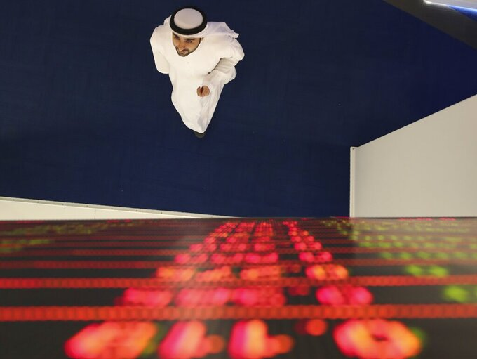 An Emirati trader checks the stocks on the screen at the Dubai Financial Market in Dubai, United Arab Emirates, Sunday, March 8, 2020. Stocks markets in the Mideast suffered sharp drops in early trading Sunday over fears about the new coronavirus and demand in crude oil falling amid a failure by OPEC and allied nations to cut production. (AP Photo/Kamran Jebreili)