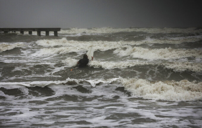 A surfer tries to paddle through the surf as wind and rain from Tropical Storm Nicholas batters the area Monday, Sept. 13, 2021, along the seawall in Galveston, Texas. (Jon Shapley/Houston Chronicle via AP)