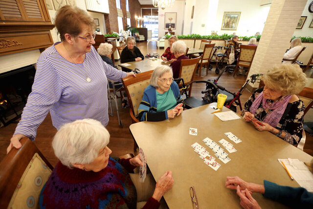 """In this Thursday, Jan. 23, 2020, photo, bridge hostess Mary Vlach, standing, visits with a table of bridge players at raceway Retirement Community in Tupelo, Miss. The hostess does all the calling to see who's coming, arrives early to set up the tables and fills in at a table if they need a sub,"""" said Vlach, 75.  (Adam Robison/The Northeast Mississippi Daily Journal via AP)"""