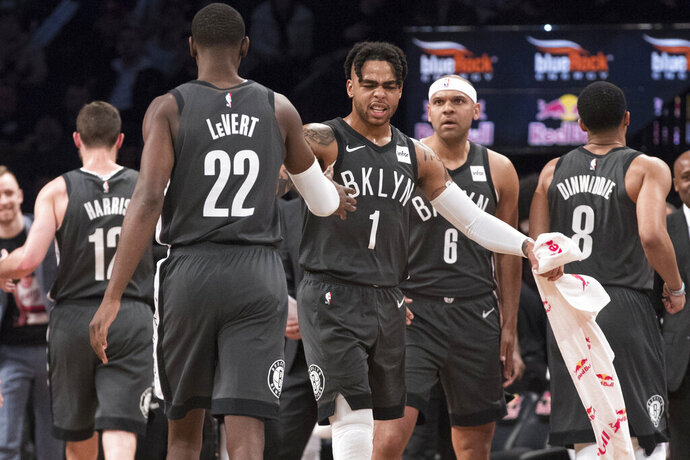 Brooklyn Nets guard D'Angelo Russell (1) and guard Caris LeVert (22) react as they go to the bench during a time out in the first half of an NBA basketball game against the Boston Celtics, Saturday, March 30, 2019, in New York. (AP Photo/Mary Altaffer)