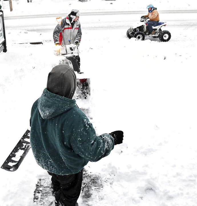 Snowblower operator Jeff Dion and his co-worker Robert Alvarado get distracted from clearing snow in front of an apartment in North Attleboro, Mass. as an ATV rider passes by Tuesday. Dec. 3, 2019. The area received several inches of new snow overnight. (Mark Stockwell/The Sun Chronicle via AP)