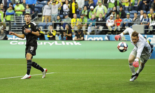 FILE - In this Wednesday, July 17, 2019 file photo, Borussia Dortmund's Gio Reyna, left, reacts after missing a shot against Seattle Sounders goalkeeper Bryan Meredith during a friendly soccer match, in Seattle. American youngster Gio Reyna's first Bundesliga start for Borussia Dortmund was foiled Saturday, May 16, 2020 by a pre-match injury. (AP Photo/Ted S. Warren, file)