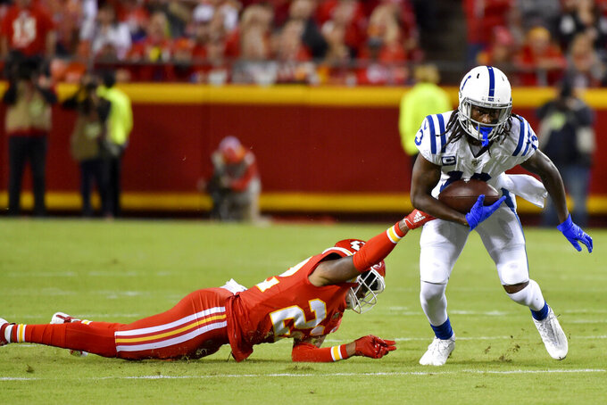 Indianapolis Colts wide receiver T.Y. Hilton (13) runs past a tackle attempt by Kansas City Chiefs safety Juan Thornhill (22) during the first half of an NFL football game in Kansas City, Mo., Sunday, Oct. 6, 2019. (AP Photo/Ed Zurga)