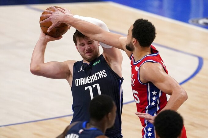 Dallas Mavericks guard Luka Doncic (77) works to keep control of the ball against Philadelphia 76ers guard Ben Simmons (25) in the first half of an NBA basketball game in Dallas, Monday, April 12, 2021. (AP Photo/Tony Gutierrez)