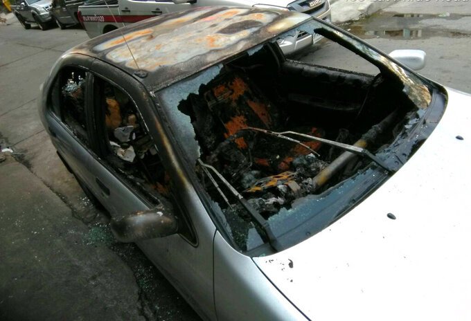 In this photo released by anti-military rule activist Ekachai Hongkangwan, the personal vehicle owned by Ekachai sits destroyed by fire on the side of a road early Monday, April 1, 2019, in Bangkok, Thailand, hours after he attended a rally calling the recent general elections mismanaged. Ekachai has been the repeated target of physical and legal attacks, including a previous one on his car that did less damage. On March 5, he was attacked by two unidentified men on a motorcycle who tried to beat him with a wooden stick and a metal pipe. (Ekachai Hongkangwan via AP)