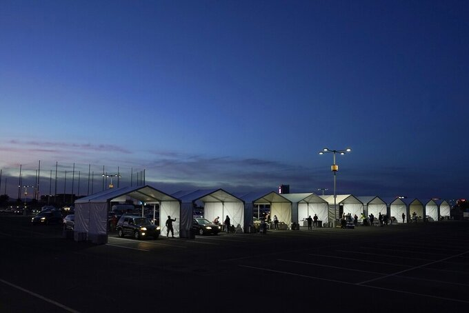 "FILE - In this Jan. 12, 2021, file photo, several tents are set up so people who have registered can get their COVID-19 vaccinations as they drive-thru the parking lot of the State Farm Stadium in Glendale, Ariz. Gov. Doug Ducey used his executive powers Monday, April 19, 2021, to prohibit local and regional governments from making ""vaccine passports"" a requirement for people to enter businesses or get services, calling it an encroachment on the private medical information of Arizona residents. (AP Photo/Ross D. Franklin, File)"