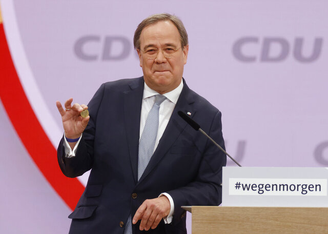 North Rhine-Westphalia's Governor and candidate as leader of the Christian Democratic Union (CDU) Armin Laschet shows a luck coin offered to him by his father as he delivers his speech on the second day of the party's 33rd congress held online because of the coronavirus pandemic, in Berlin on January 16, 2021. German Chancellor Angela Merkel's party is choosing a new leader on Saturday, eight months before voters decide who will succeed Merkel in a national election. (Odd Andersen/Pool via AP)