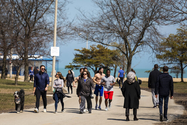 People enjoying warm weather with a stroll along the Lakefront Trail Trail near North Avenue Beach, Wednesday afternoon, March 25, 2020, in Chicago, despite a stay-at-home order from Illinois Gov. J.B. Pritzker during the coronavirus pandemic. The new coronavirus causes mild or moderate symptoms for most people, but for some, especially older adults and people with existing health problems, it can cause more severe illness or death.  (Ashlee Rezin Garcia/Chicago Sun-Times via AP)