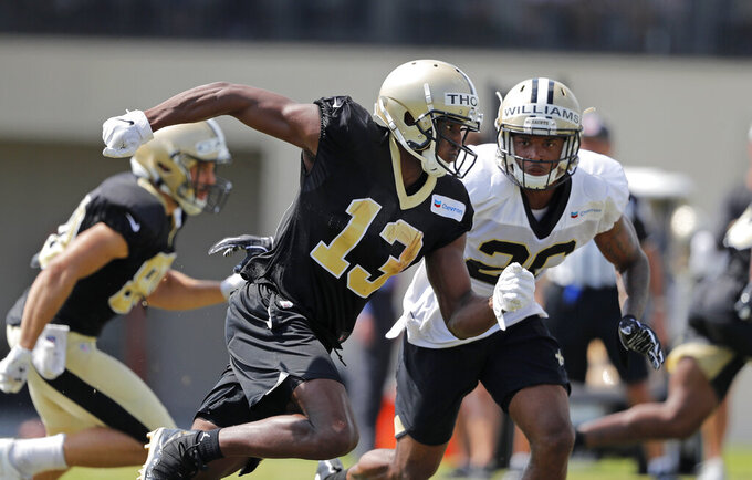 New Orleans Saints wide receiver Michael Thomas (13) runs drills against cornerback P.J. Williams (26) during training camp at their NFL football training facility in Metairie, La., Thursday, Aug. 1, 2019. (AP Photo/Gerald Herbert)