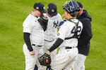New York Yankees starting pitcher Nick Nelson talks to teammates and pitching coach Matt Blake, right, during the first inning of a baseball game against the Tampa Bay Rays Friday, April 16, 2021, in New York. (AP Photo/Frank Franklin II)