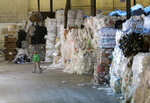 In this May 7, 2019 photo, a man walks under towers of recyclables at a GDB International warehouse in Monmouth Junction, N.J. A decision by China's government to restrict imports of wastepaper and plastic that has disrupted U.S. recycling programs has also spurred investment in American plants that process recyclables. (AP Photo/Seth Wenig)