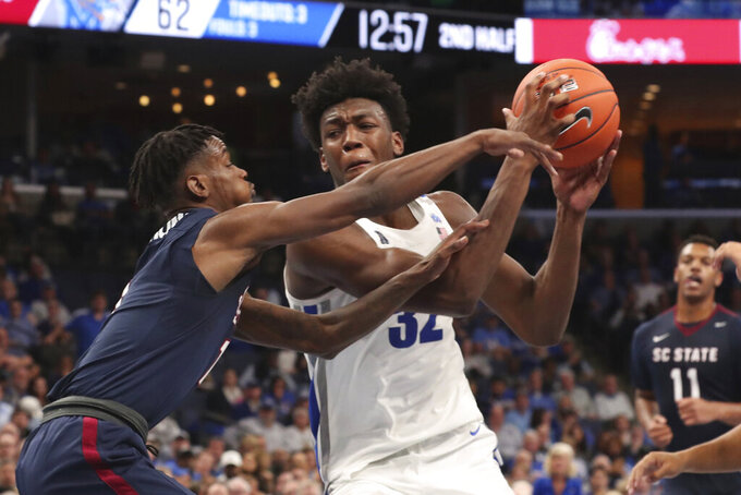 Memphis' James Wiseman keeps the ball away from South Carolina State's Tariq Simmons (1) during the second half of an NCAA college basketball game Tuesday, Nov. 5, 2019, in Memphis, Tenn. (AP Photo/Karen Pulfer Focht)