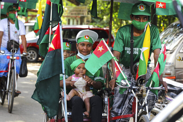 A supporter of the military-backed Union Solidarity and Development Party (USDP) holds a toddler while onboard a trishaw during an election campaign motorcade in Yangon, Myanmar, on Thursday, Nov. 5, 2020. Myanmar's citizens go to the polls Sunday, Nov. 8, in an effort to sustain the fledgling democracy they helped install just five years ago. (AP Photo/Thein Zaw)
