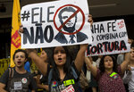 FILE - In this Oct. 26, 2018 file photo, university students hold signs with messages that read in Portuguese: