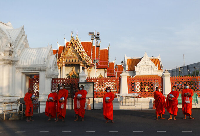 Buddhist monks wearing face masks to protect themselves from the coronavirus wait in line to receive alms during a morning alms offerings in front of Marble Temple in Bangkok, Thailand, Friday, April 16, 2021. (AP Photo/Sakchai Lalit)