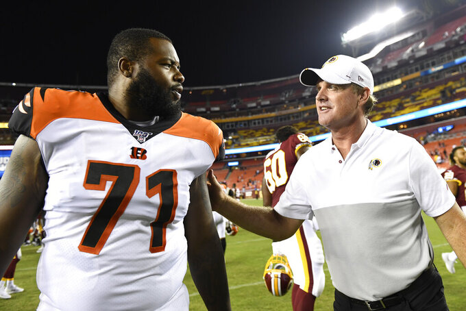 Washington Redskins coach Jay Gruden, right, talks with Cincinnati Bengals offensive tackle Andre Smith  at the end of an NFL preseason football game in Landover, Md., Thursday, Aug. 15, 2019. The Bengals won 23-13. (AP Photo/Susan Walsh)