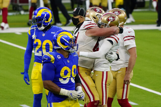 San Francisco 49ers kicker Robbie Gould, second from right, is hugged by teammates after making a game-winning field goal during the second half of an NFL football game against the Los Angeles Rams Sunday, Nov. 29, 2020, in Inglewood, Calif. (AP Photo/Alex Gallardo)