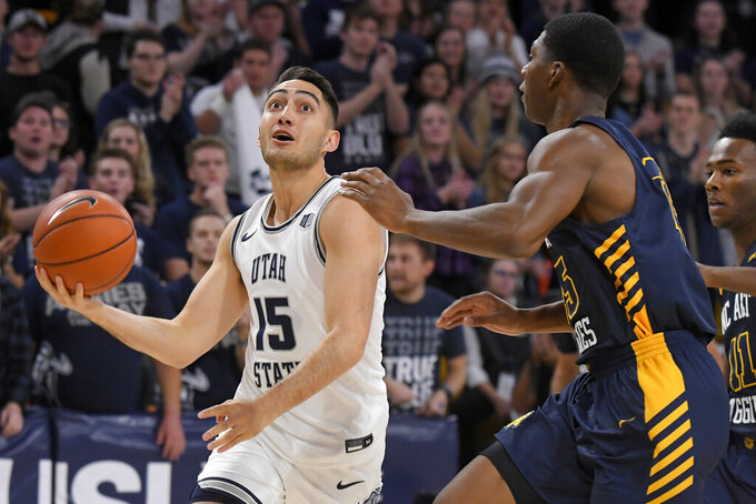 Utah State guard Abel Porter (15) drives to the basket as North Carolina A&T forward Webster Filmore defends during the first half of an NCAA college basketball game Friday, Nov. 15, 2019, in Logan, Utah. (AP Photo/Eli Lucero)