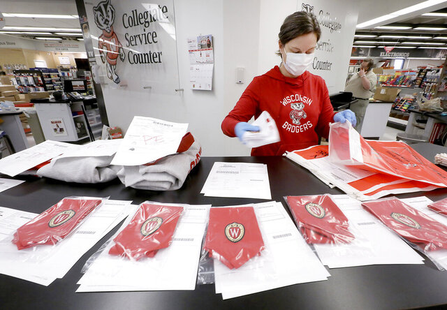 In this Tuesday, May 5, 2020 photo, University of Wisconsin Bookstore worker Stephanie Blaser packages GPA honor stoles purchased by UW-Madison graduates at the store's State Street location in Madison, Wis. Although this year's traditional commencement ceremony has been postponed due to the coronavirus pandemic, the store is shipping caps, gowns and stoles to students now and allowing them to keep the items until a rescheduled event is held. (John Hart/Wisconsin State Journal via AP)