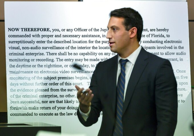 Alex Spiro, attorney for New England Patriots owner Robert Kraft, stands in front of a copy of a search warrant as he questions Jupiter Police Detective Andrew Sharp during a motion hearing in the Kraft prostitution solicitation case, Wednesday, May 1, 2019, in West Palm Beach, Fla. Kraft's attorneys argue that undercover surveillance videos allegedly showing their client paying for sex at a Jupiter day spa should be ruled inadmissible and the evidence thrown out. (Lannis Waters/Palm Beach Post via AP, Pool)