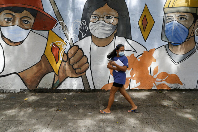 A woman wearing protective mask to prevent the spread of the coronavirus walk past a mural showing frontliners in Manila, Philippines on Wednesday, Oct. 21, 2020. The Philippines lifted a ban on non-essential foreign trips by Filipinos Wednesday but the immigration bureau said the move did not immediately spark large numbers of departures for tourism and leisure. (AP Photo/Aaron Favila)