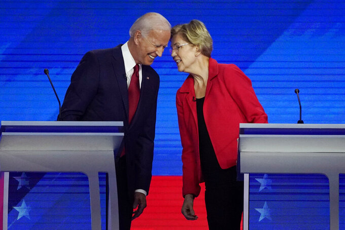 FILE - In this Sept. 12, 2019, file photo Democratic presidential candidates former Vice President Joe Biden, left and Sen. Elizabeth Warren, D-Mass., talk during a Democratic presidential primary debate hosted by ABC at Texas Southern University in Houston. Warren, a Massachusetts senator and leading progressive, has become an unlikely confidant and adviser to Biden, the presumptive Democratic presidential nominee. They talk every 10 days or so, according to aides to both politicians who requested anonymity to describe their relationship. (AP Photo/David J. Phillip, File)