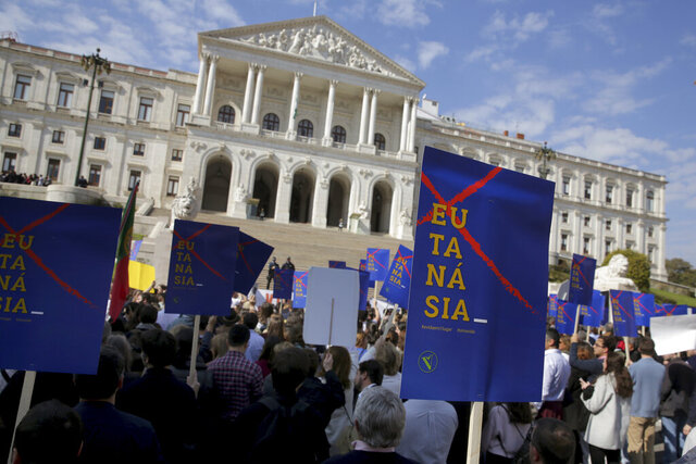 Demonstrators protest outside the Portuguese parliament in Lisbon, Thursday, Feb. 20, 2020. Protesters gathered Thursday outside Portugal's where lawmakers were due to debate proposals that would allow euthanasia and doctor-assisted suicide. Groups which oppose the procedures waved banners and chanted