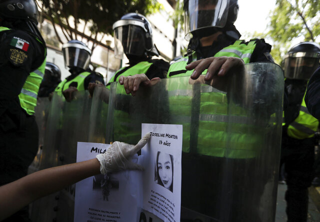 FILE - In this June 7, 2020 file photo, a demonstrator sticks a flyer of a women who was a victim of violence on the riot shield of police officer outside Mexico City's security headquarters during a protest amid the COVID-19 pandemic in Mexico City. New government figures show the number of homicides in Mexico has grown during the new coronavirus pandemic, including a 9.2% spike in killings of women, according to data released Monday, July 20.  (AP Photo/Fernando Llano, File)