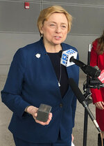 Maine Gov. Janet Mills holds a 1-pound block of carbon to make her point as she talks about her decision to support a transmission project that would bring Canadian hydropower to Massachusetts residents, on Thursday, Feb. 21, 2019, in Portland, Maine. Mills spoke at the Portland Jetport before heading to the nation's capital to attend the annual National Governors Association winter meeting. (AP Photo/David Sharp)