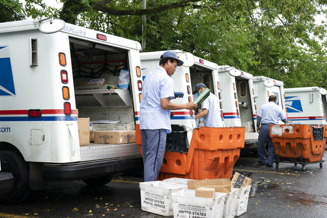 FILE - In this July 31, 2020, file photo, letter carriers load mail trucks for deliveries at a U.S. Postal Service facility in McLean, Va. A U.S. judge on Thursday, Sept. 17, 2020, blocked controversial Postal Service changes that have slowed mail nationwide. The judge called them