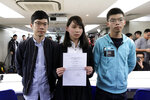 In this Jan. 27, 2018, photo, Agnes Chow, center, a member of democracy Demosisto party, is accompanied by Joshua Wong, right, and Nathan Law, holds a notice from the Hong Kong government at a press conference in Hong Kong. After a security law for Hong Kong passed in China, prominent Hong Kong pro-democracy activists Wong, Chow an Law issued statements on Facebook on Tuesday, June 30, 2020, saying they would withdraw from the pro-democracy organization Demosisto. Wong said