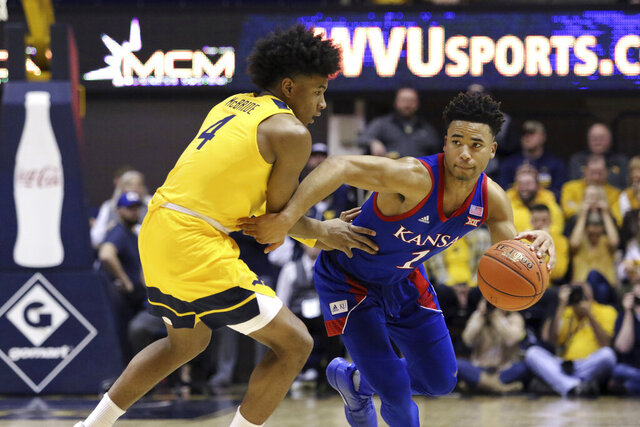 Kansas guard Devon Dotson (1) is defended by West Virginia guard Miles McBride (4) during the first half of an NCAA college basketball game Wednesday, Feb. 12, 2020, in Morgantown, W.Va. (AP Photo/Kathleen Batten)
