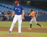 Toronto Blue Jays starting pitcher Clayton Richard, left, kicks dirt on the mound after giving up a two-run home run to Baltimore Orioles' Renato Nunez, right, in the fourth inning of a baseball game in Toronto, Saturday, July 6, 2019. (Fred Thornhill/The Canadian Press via AP)