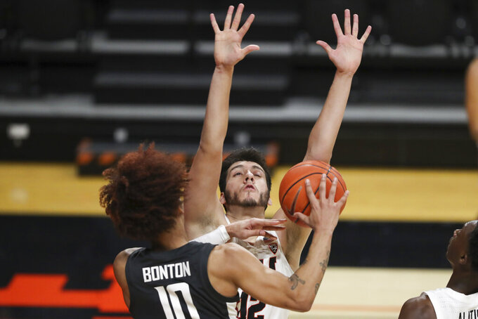 Oregon State's Roman Silva (12) blocks a shot by Washington State's Isaac Bonton (10) during the second half of an NCAA college basketball game in Corvallis, Ore., Saturday, Feb. 6, 2021. (AP Photo/Amanda Loman)