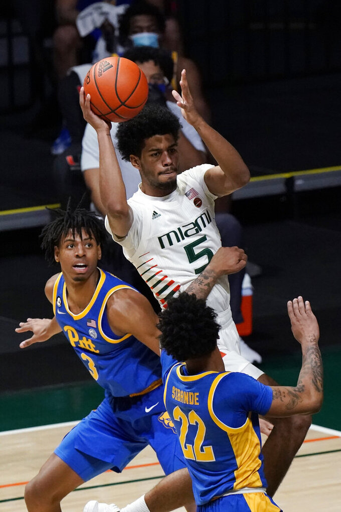 Miami guard Harlond Beverly (5) looks for an opening past Pittsburgh forward Noah Collier (3) and guard Nike Sibande (22) during the first half of an NCAA college basketball game, Wednesday, Dec. 16, 2020, in Coral Gables, Fla. (AP Photo/Wilfredo Lee)