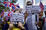 FILE- In this Sunday, Sept. 15, 2019, file photo, protesters hold placards and wave British flags during a peaceful demonstration outside the British Consulate in Hong Kong. The British government said Thursday, April 8, 2021, it is setting up a 43 million pound ($59 million) fund to help migrants from Hong Kong settle in the country as they escape increasing political repression in the former colony. (AP Photo/Vincent Yu)