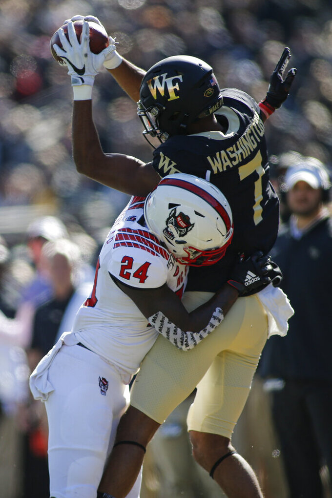 Wake Forest wide receiver Scotty Washington, right, catches a pass out of bounds against North Carolina State cornerback Malik Dunlap in the first half of an NCAA college football game in Winston-Salem, N.C., Saturday, Nov. 2, 2019. Wake Forest won 44-10. (AP Photo/Nell Redmond)