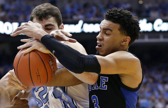 North Carolina's Luke Maye, left, and Duke's Tre Jones (3) struggle for possession of the ball during the first half of an NCAA college basketball game in Chapel Hill, N.C., Saturday, March 9, 2019. (AP Photo/Gerry Broome)