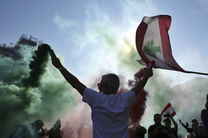 Anti-government protesters wave Lebanese national flags as they gather during a separate civil parade at the Martyr square, in downtown Beirut, Lebanon, Friday, Nov. 22, 2019.  Protesters gathered for alternative independence celebrations, converging by early afternoon on Martyrs' Square in central Beirut, which used to be the traditional location of the official parade. Protesters have occupied the area, closing it off to traffic since mid-October (AP Photo/Hassan Ammar)