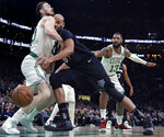Minnesota Timberwolves forward Taj Gibson, center, collides with Boston Celtics forward Gordon Hayward, left, during the first quarter of an NBA basketball game in Boston, Wednesday, Jan. 2, 2019. At rear right is Celtics forward Marcus Morris (13). (AP Photo/Charles Krupa)